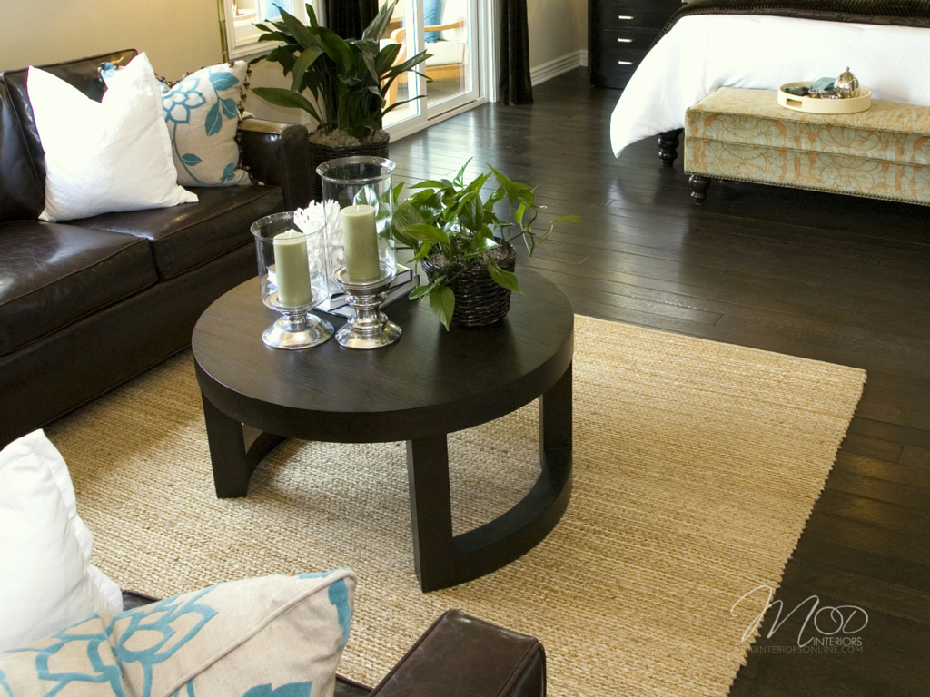 Master bedroom seating area, with tan color walls, textured rug and brown leather furniture